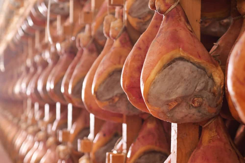 This is a close look at a ham factory with rows of ham hanging to season.