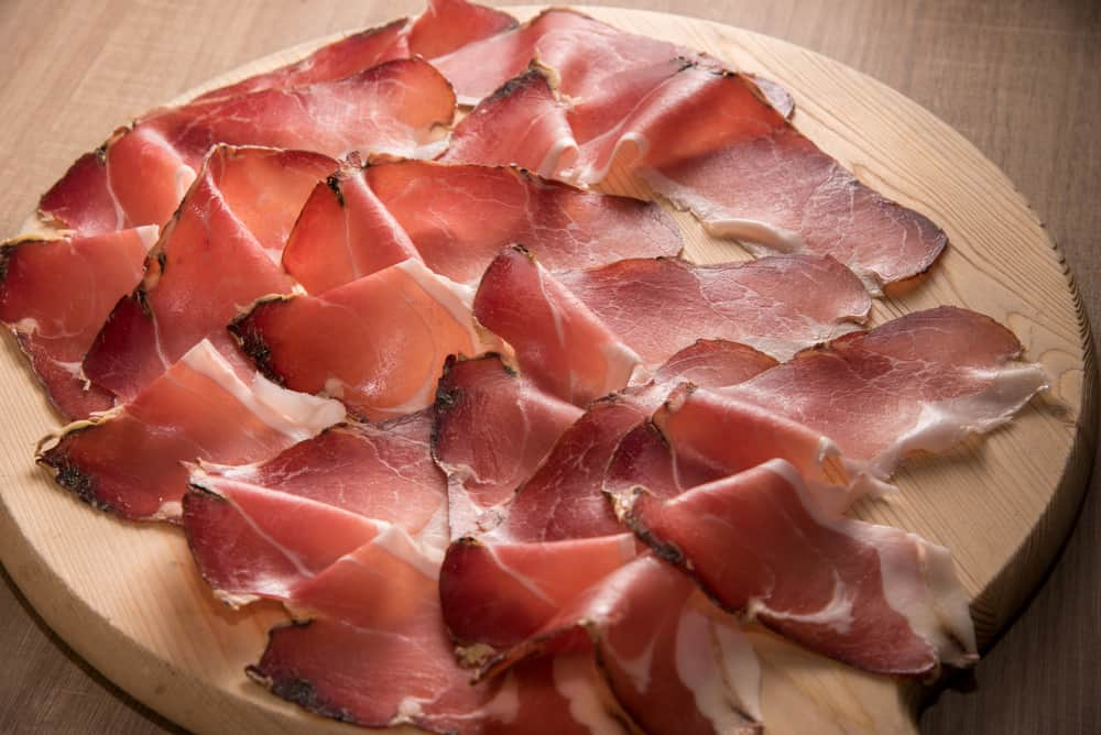 This is a close look at slices of speck Italian ham on a chopping board.