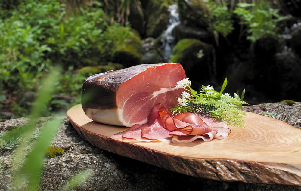 This is a close look at a piece of black forest ham on a wooden plank.