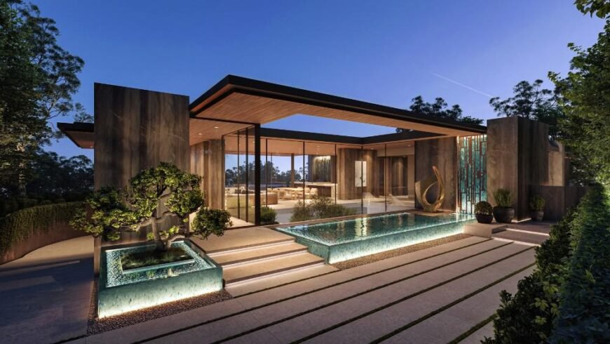 This is an exterior look at the house that has glass walls and glass ceiling with a clear view of the interior open plan design. This is then complemented by the landscaping of shrubs and water features with lighting.
