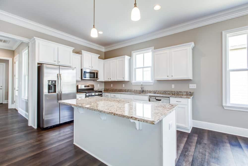 Kitchen with white cabinets, stainless steel appliances, and a breakfast island.