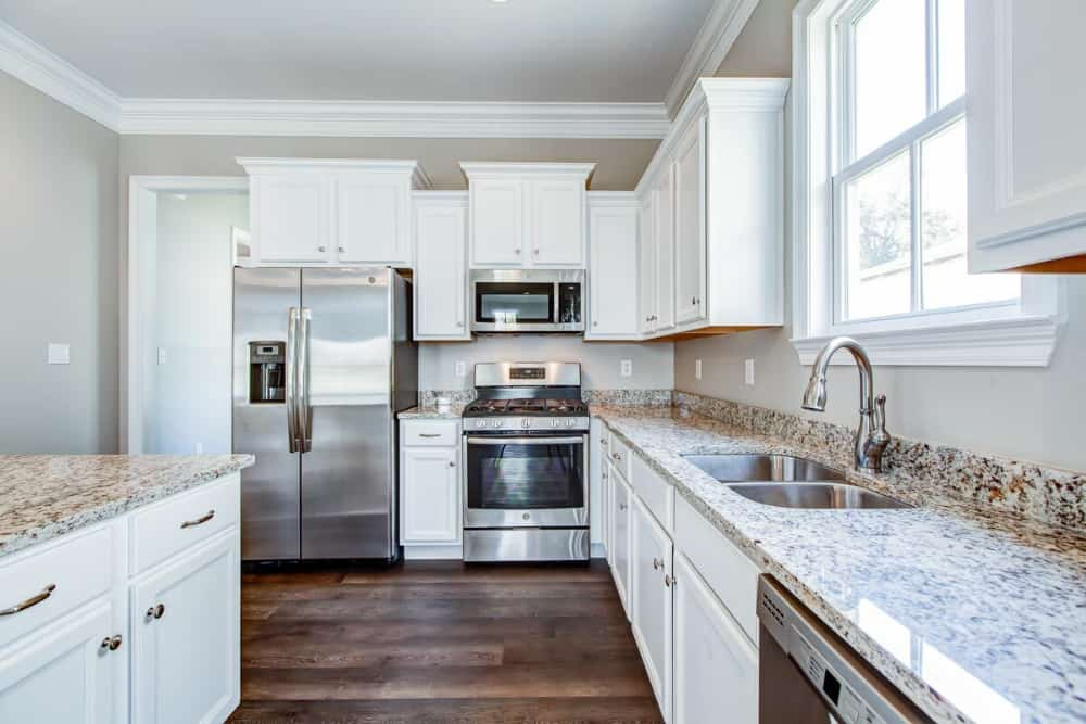 The kitchen includes a double bowl sink paired with a gooseneck faucet.