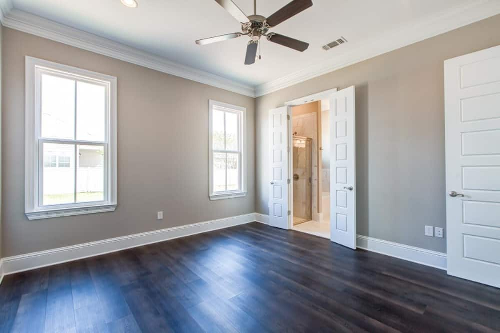 Primary bedroom with dark hardwood floor, a ceiling fan, and a private bath.