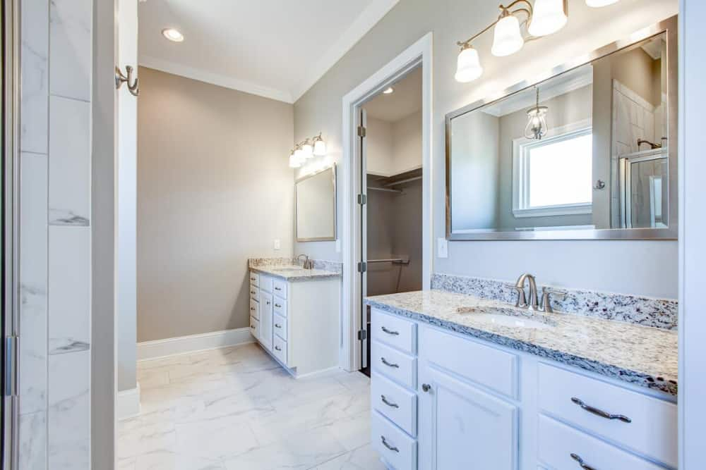 The primary bathroom features his and her sink vanities flanking the walk-in closet.