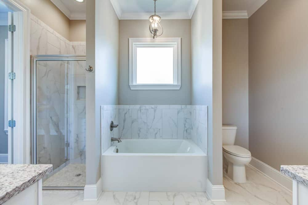 Across the vanities are the toilet, drop-in tub, and walk-in shower.