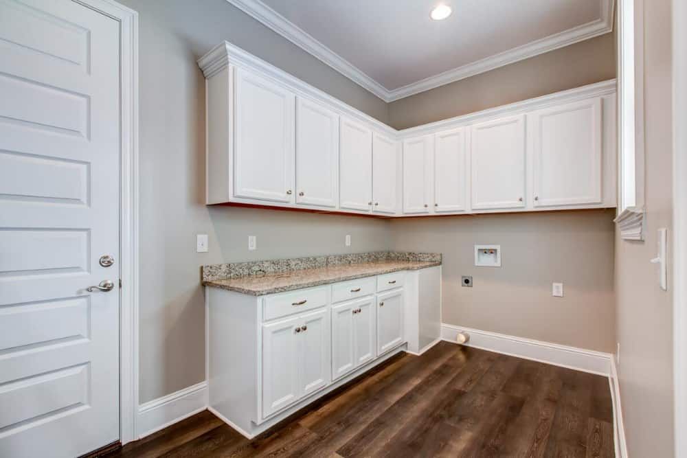 Laundry room with granite countertop and white cabinets fixed against the beige walls.