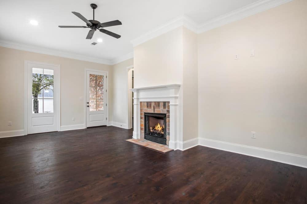 Living room with a wrought iron ceiling fan and a brick fireplace bordered with a white mantel.