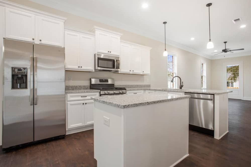 Kitchen with stainless steel appliances, granite countertops, white cabinetry, and a center island.