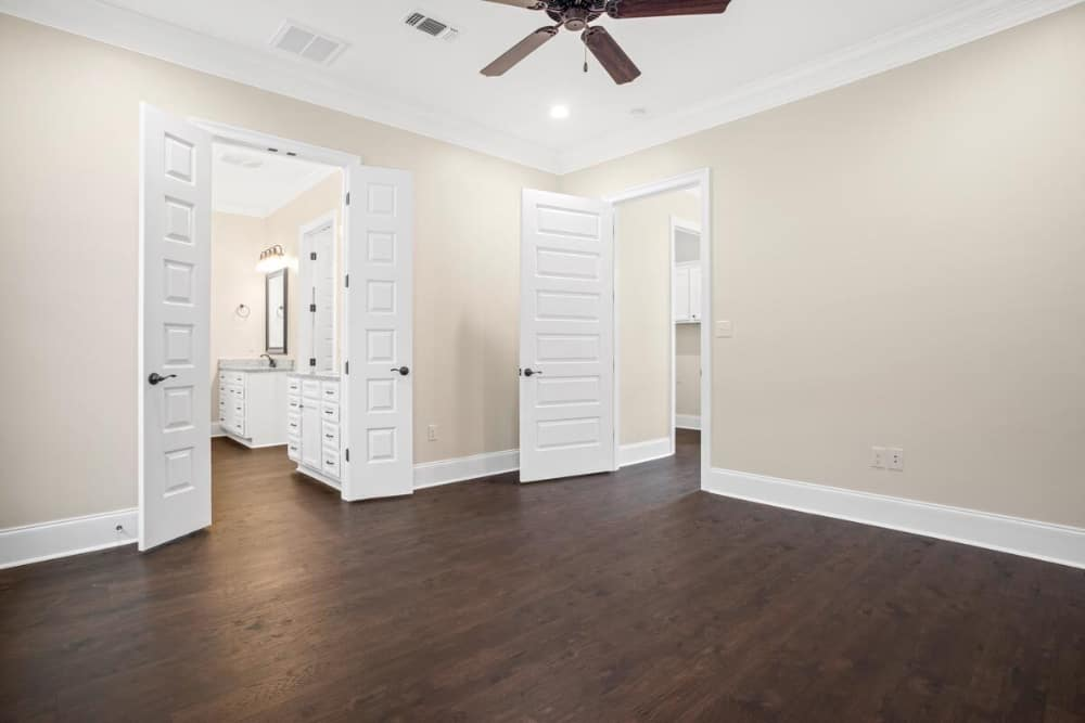 Primary bedroom with dark hardwood flooring, beige walls, and a white double door that opens to the primary bath.