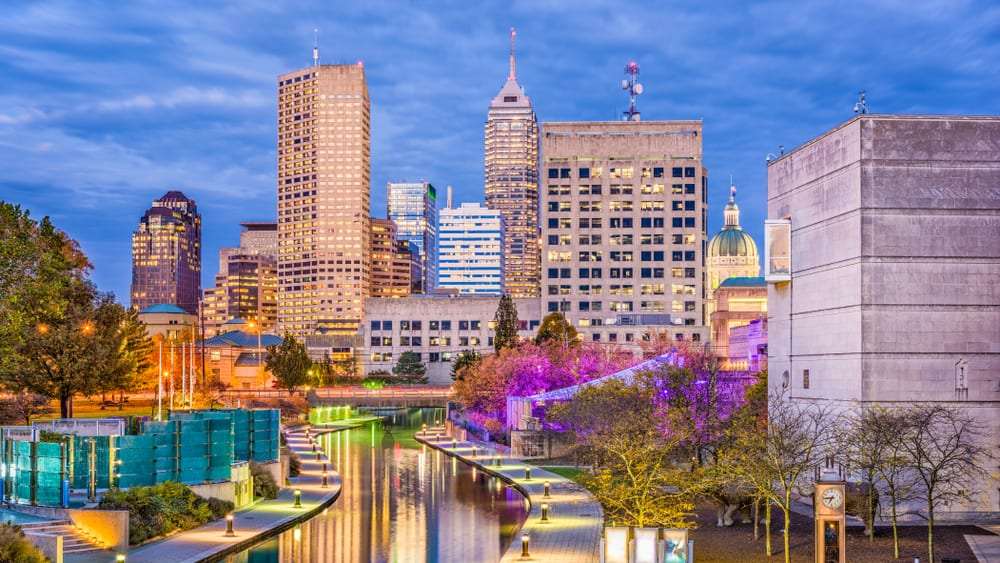 This is a full nighttime view of the Indianapolis, Indiana skyline and canal.