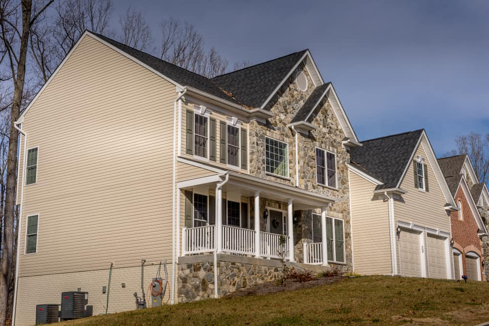 This is a close look at the American colonial luxury home with entry porch and a front loading garage.