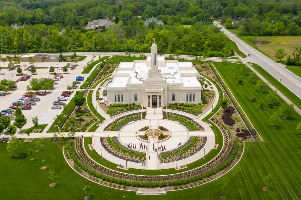This is an aerial view of the Indianapolis, Indiana Temple showcasing large grass lawns and a large bright beige building.