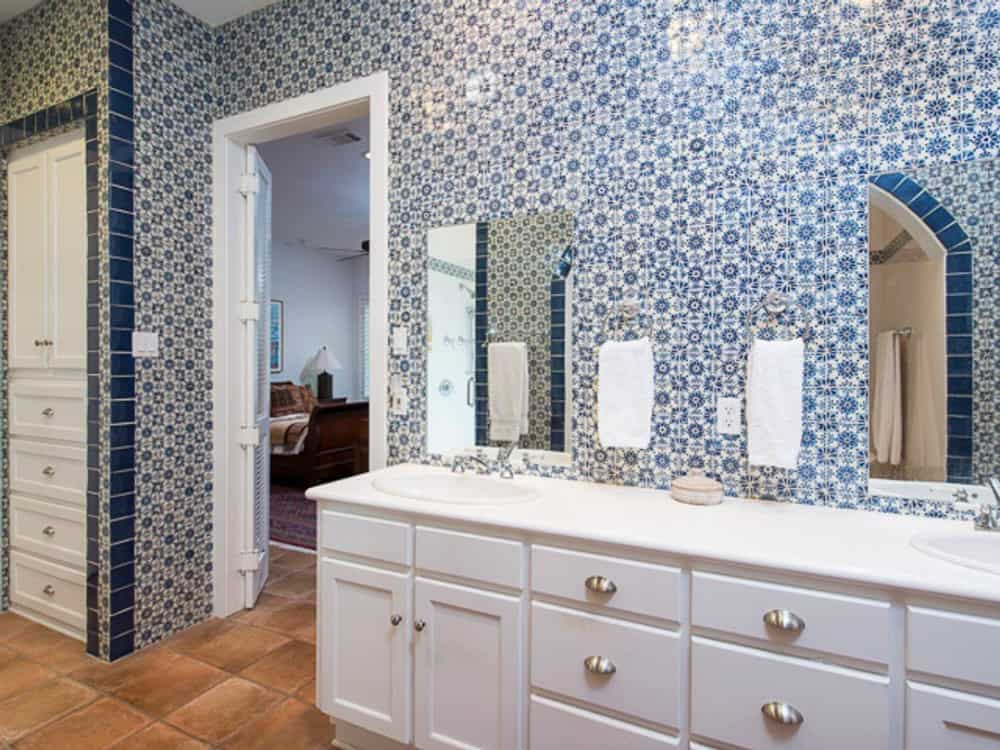 The primary bathroom includes a dual sink vanity paired with frameless mirrors.
