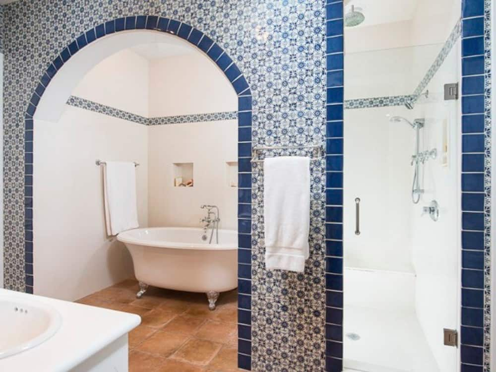Primary bathroom with a walk-in shower and a clawfoot tub framed with a decorative archway.
