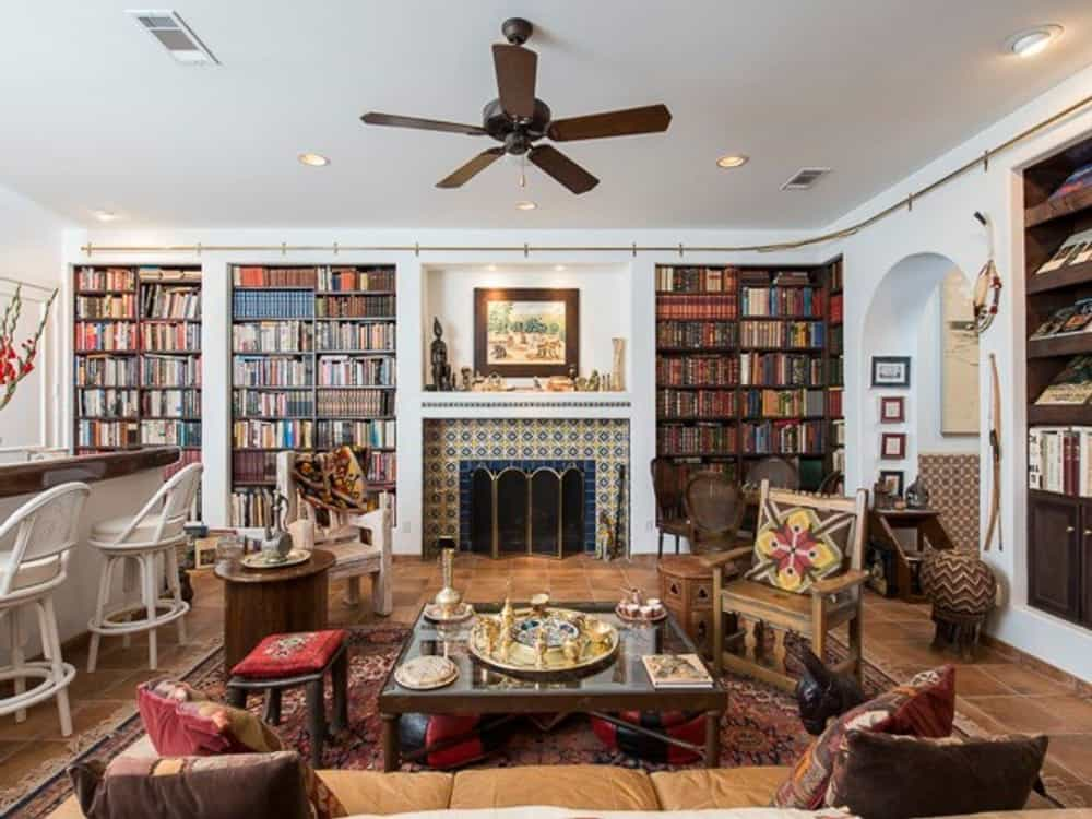 The living room is filled with a fireplace, built-in bookcases, cozy seats, and a wet bar.
