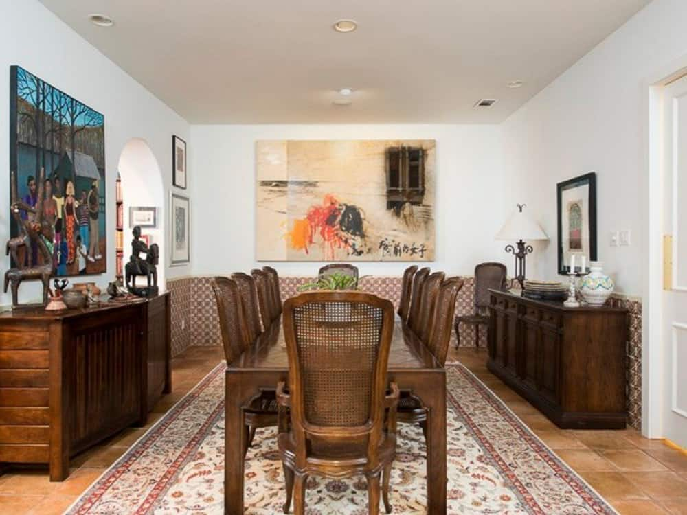 Formal dining room with a classic area rug, a 10-seater dining set, and matching buffet tables adorned with lovely artworks.
