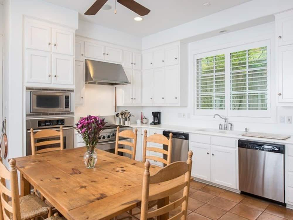 Eat-in kitchen with stainless steel appliances, white cabinetry, and wooden dining set over terracotta flooring.