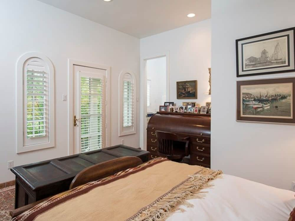 Bedroom with dark wood furnishings, arched windows, and beige walls adorned with framed artworks.