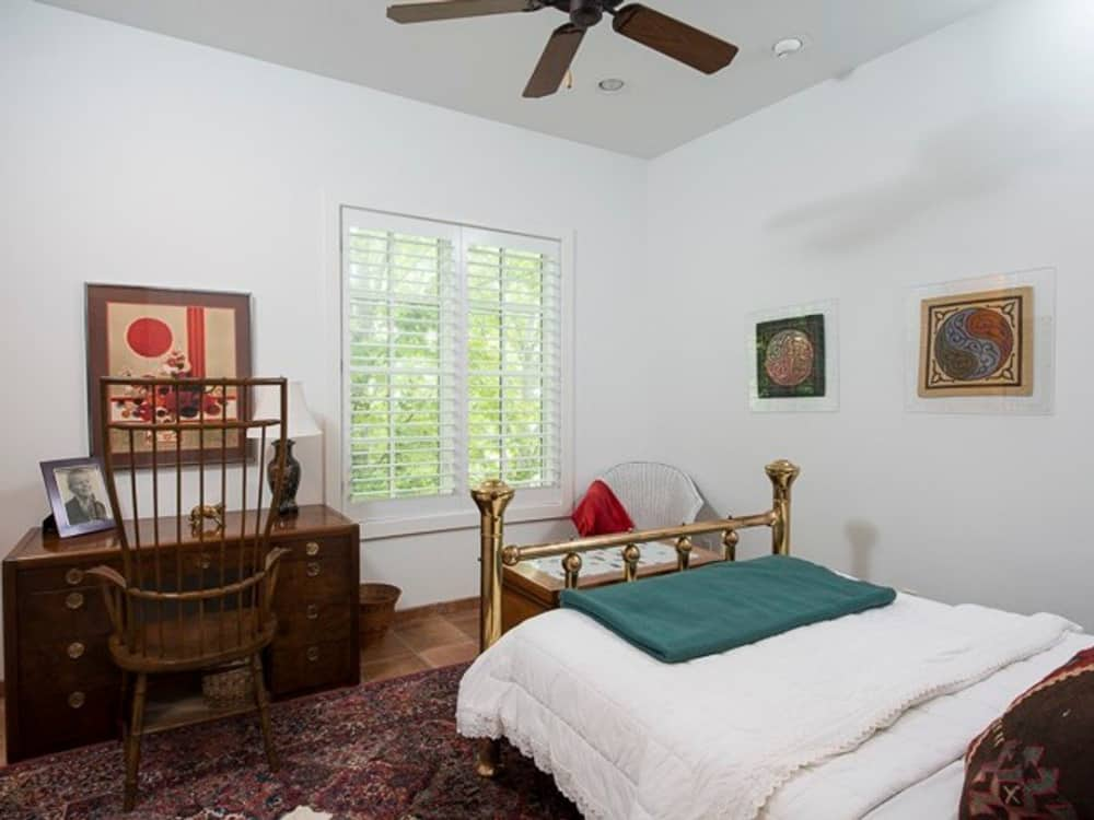 Another bedroom with a wooden desk, a copper bed, and a vintage area rug that lays on the terracotta floor.