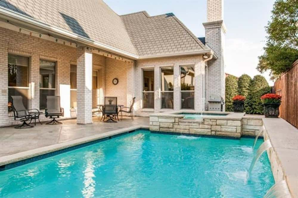 Side patio with metal chairs and a sparkling pool integrated with a built-in spa.