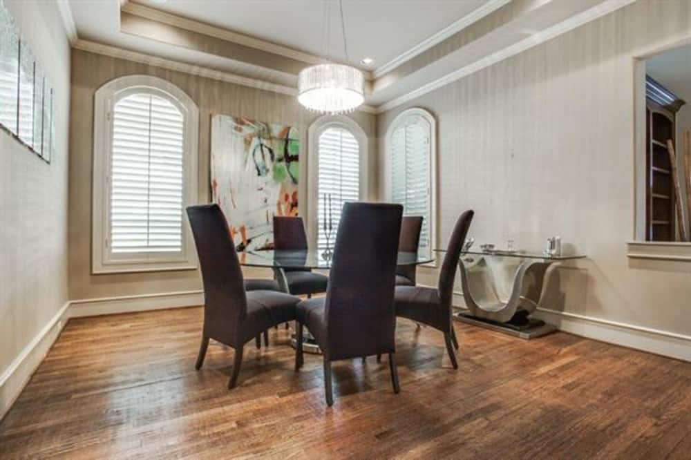 Formal dining room with arched windows, a round dining set, and a glass top buffet table over the hardwood flooring.