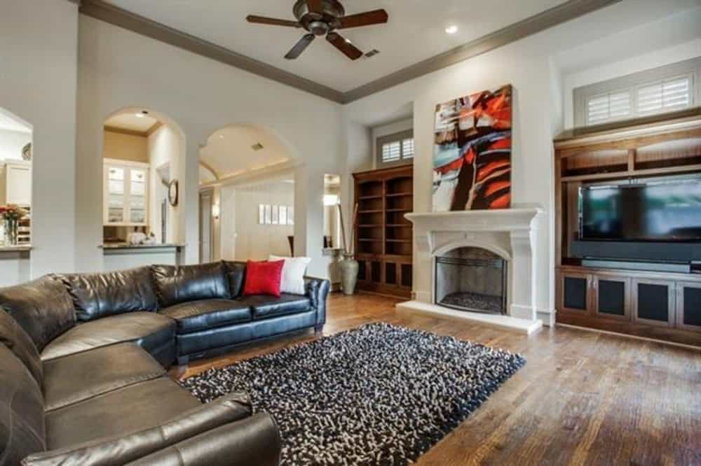 The family room includes a TV and a fireplace topped with an abstract painting.