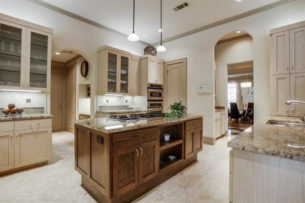 Kitchen with light wood cabinets, granite countertops, and a center island fitted with a built-in cooktop.