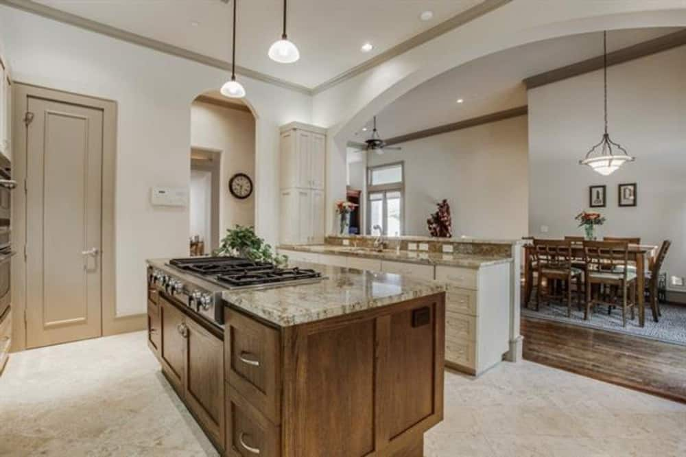 The kitchen overlooks the breakfast area with a rectangular dining set.