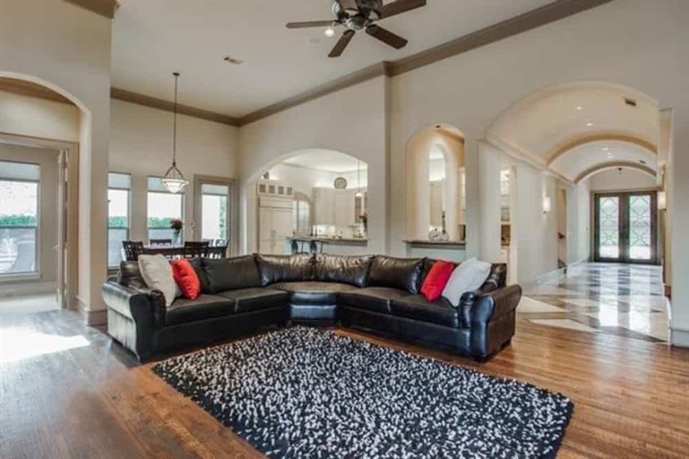 Family room with a shaggy area rug and a black leather sectional accentuated with bold throw pillows.