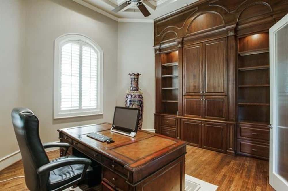 Study with a wooden cabinet and a matching desk paired with a leather armchair.