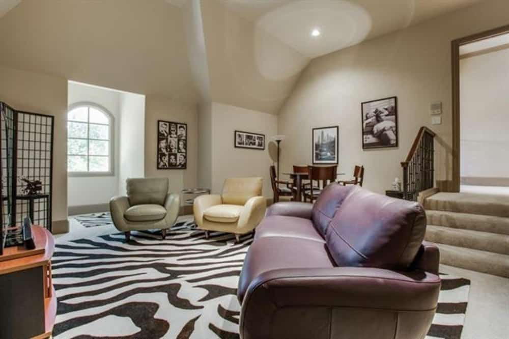 Bonus room with contemporary seats, a large zebra rug, and framed artworks gracing the beige walls.