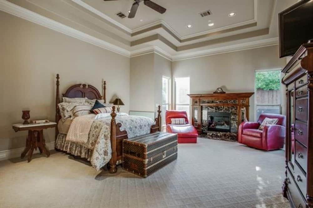 The primary bedroom features a step ceiling, a four-poster bed, and a marble fireplace flanked by red leather seats.
