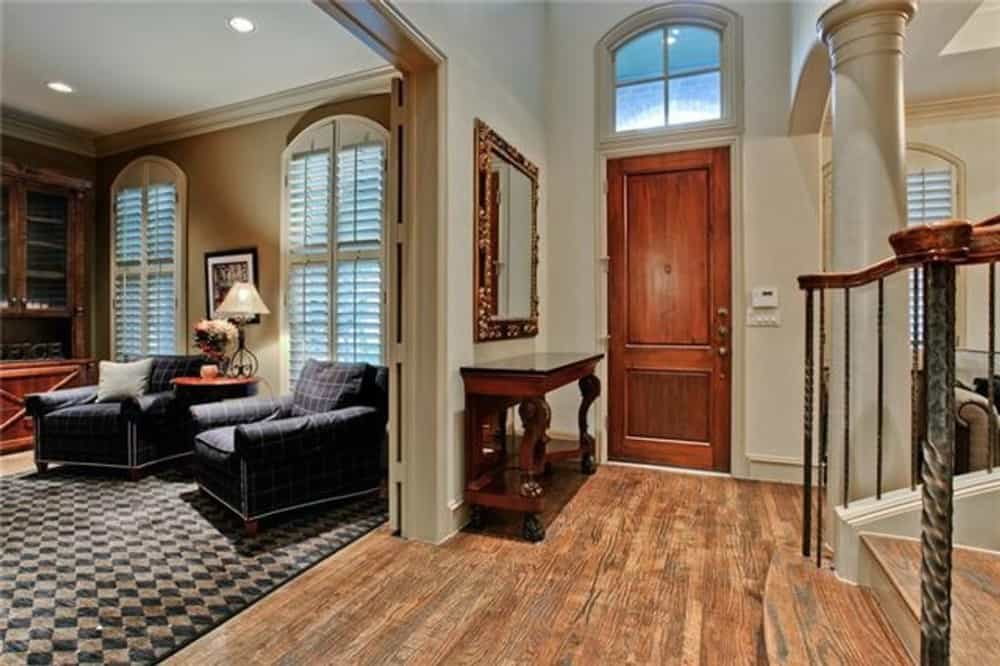 The foyer has an arched transom and a dark wood console table topped with a decorative mirror.