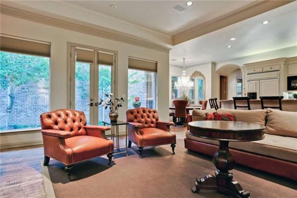 Family room with a leather sofa, tufted armchairs, and a round table over a bordered area rug.