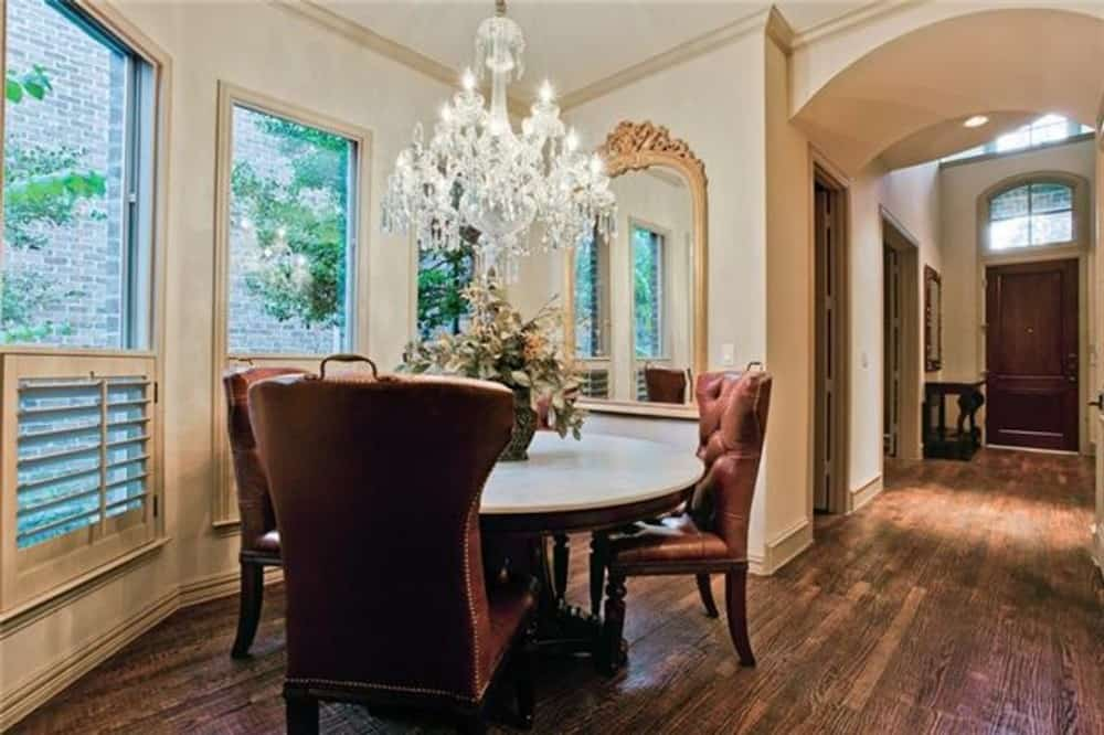 Breakfast nook with a bay window and round dining set illuminated by a crystal chandelier.