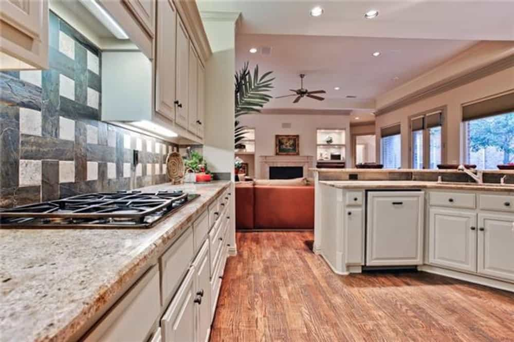 Kitchen with white cabinets, granite countertops, and a built-in cooktop.