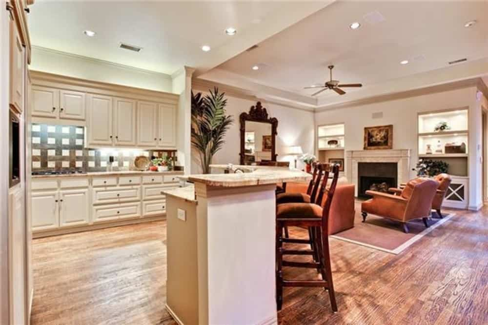 The kitchen includes a curved island integrated with a raised eating bar.