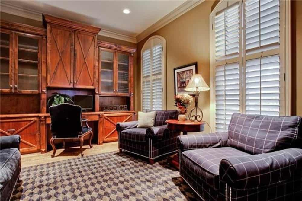 Living room with plaid armchairs and a built-in desk topped with overhead cabinets.