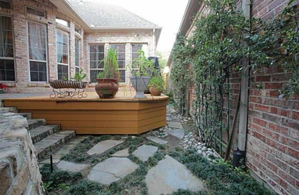 The patio features a wooden deck graced with potted plants.