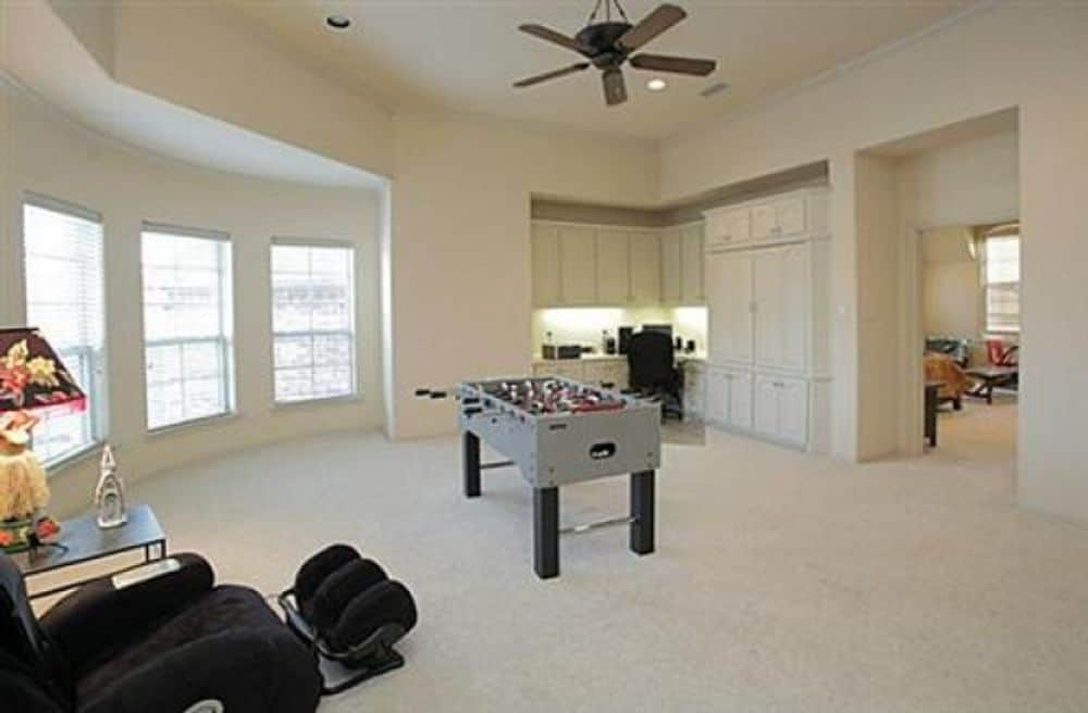Recreation room with a black recliner, a game table, white cabinets, and a bow window.