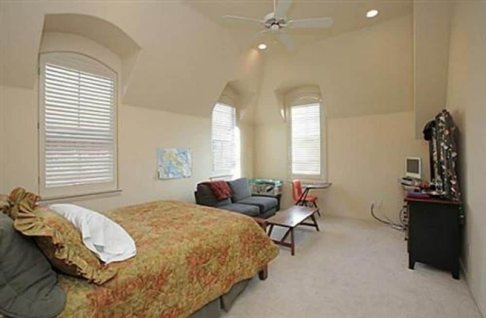 Another bedroom with beige walls, arched windows, a cozy bed, and a gray sofa paired with a wooden table.