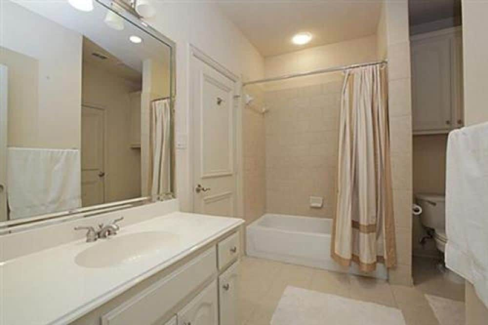 This bathroom offers a single sink vanity and a tub and shower combo enclosed in a beige curtain.