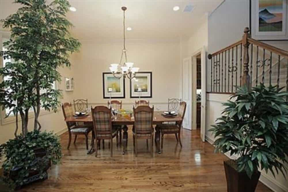 Dining area with a rectangular dining set, a classic chandelier, and framed artwork adorning the beige walls.