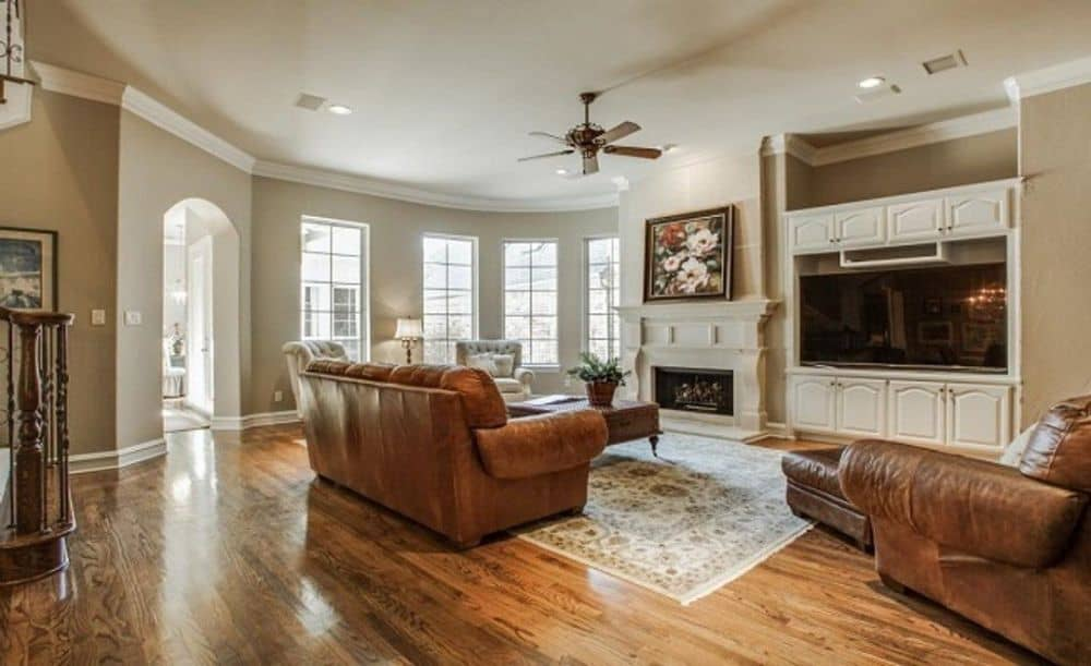 Family room with leather seats, a fireplace, and a large TV.