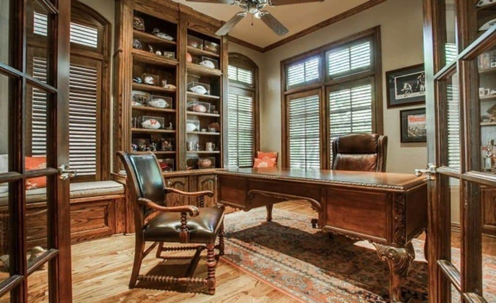 A wooden french door opens into the study filled with a built-in bookcase, a window seat, and a wooden desk paired with leather chairs.