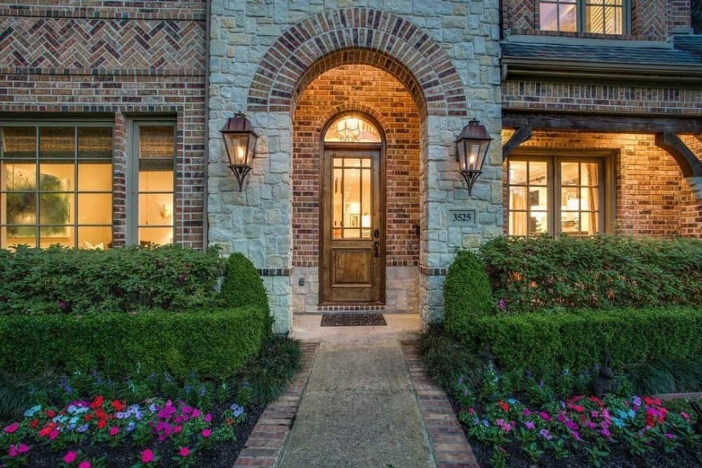 Home entry with a stone archway and a glazed front door topped with an arched transom.