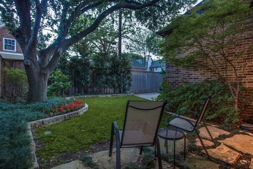 Open patio with a lush green lawn, tall plants, and metal armchairs.