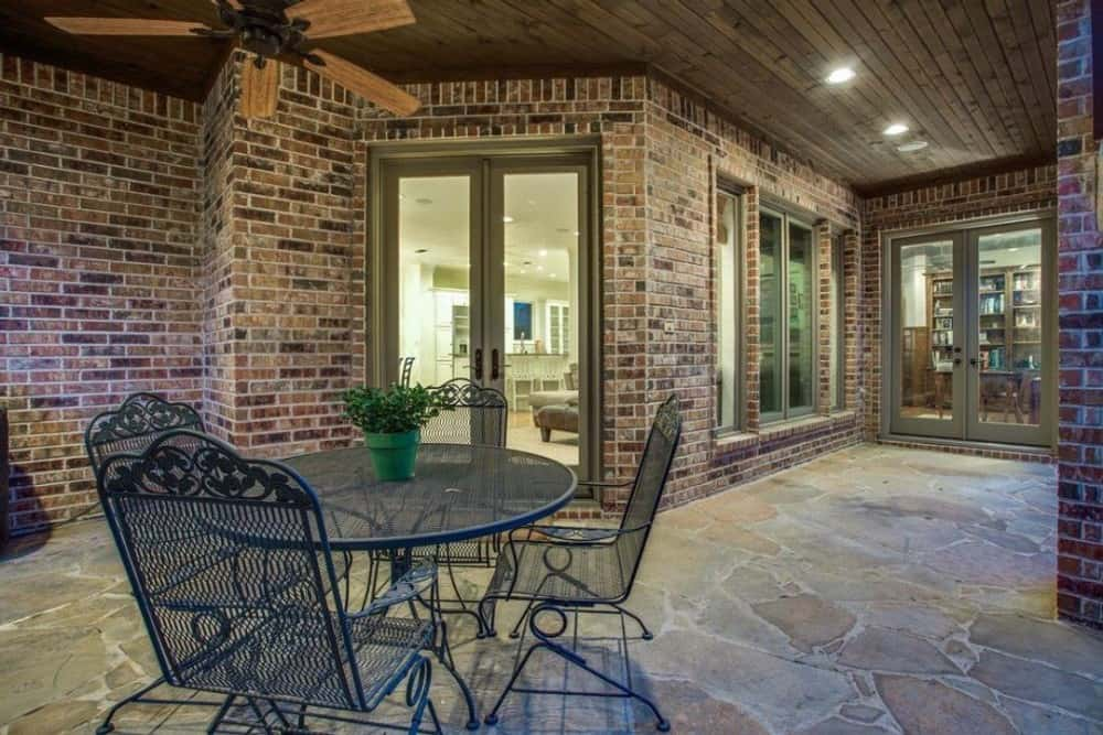 Covered porch with a ceiling fan and a round, outdoor dining set over flagstone flooring.