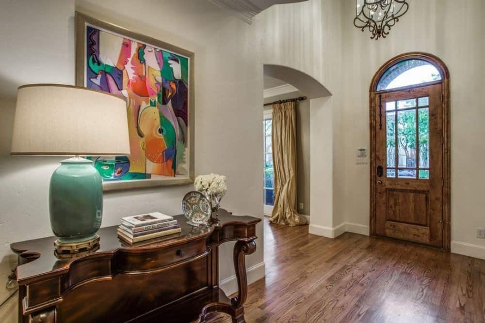The foyer has a wooden console table topped with a large table lamp and lovely artwork.