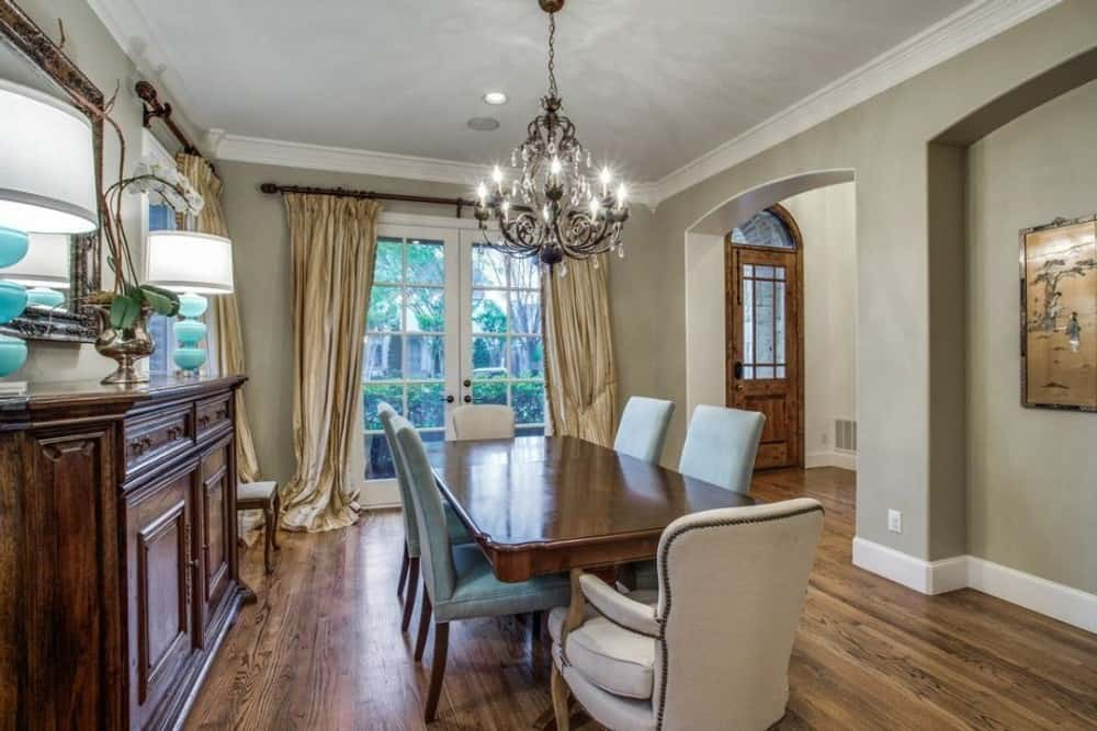 Formal dining room with a 6-seater dining set, a matching buffet table, and a french door dressed in classy drapes.